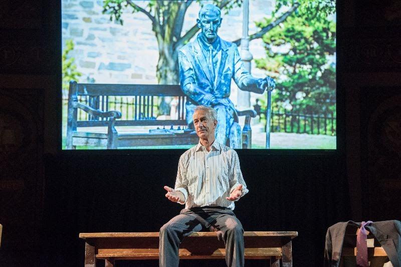 Karski sitting on his desk talking to the audience.