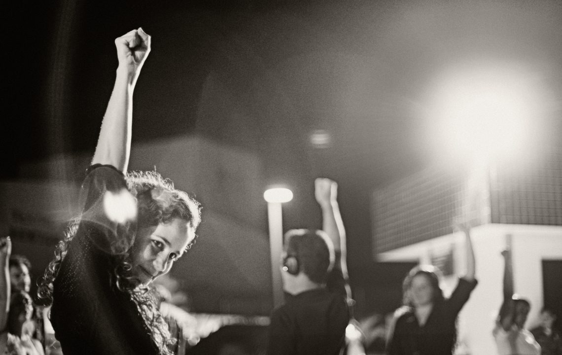 image description: in foreground: a woman, wearing headphones, with her fist in the air. In background: more people—all with headphones on—with their fists raised.