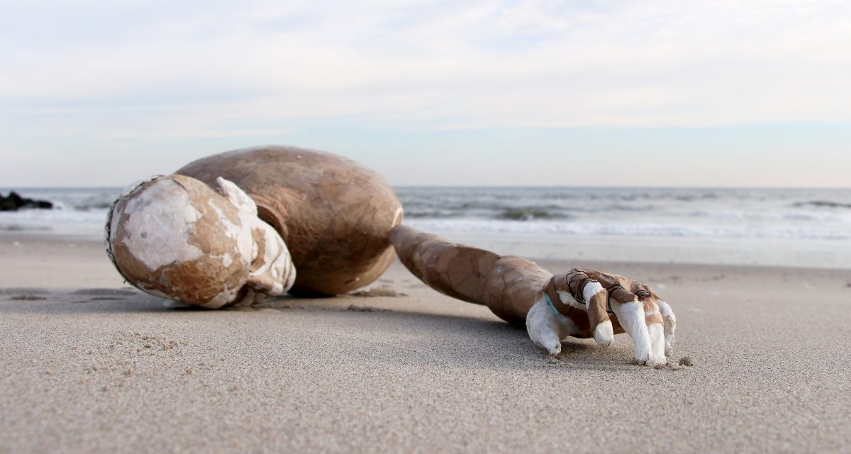 Image description: a mannequin washed on the shore of the beach, its arm stretched out towards the camera.