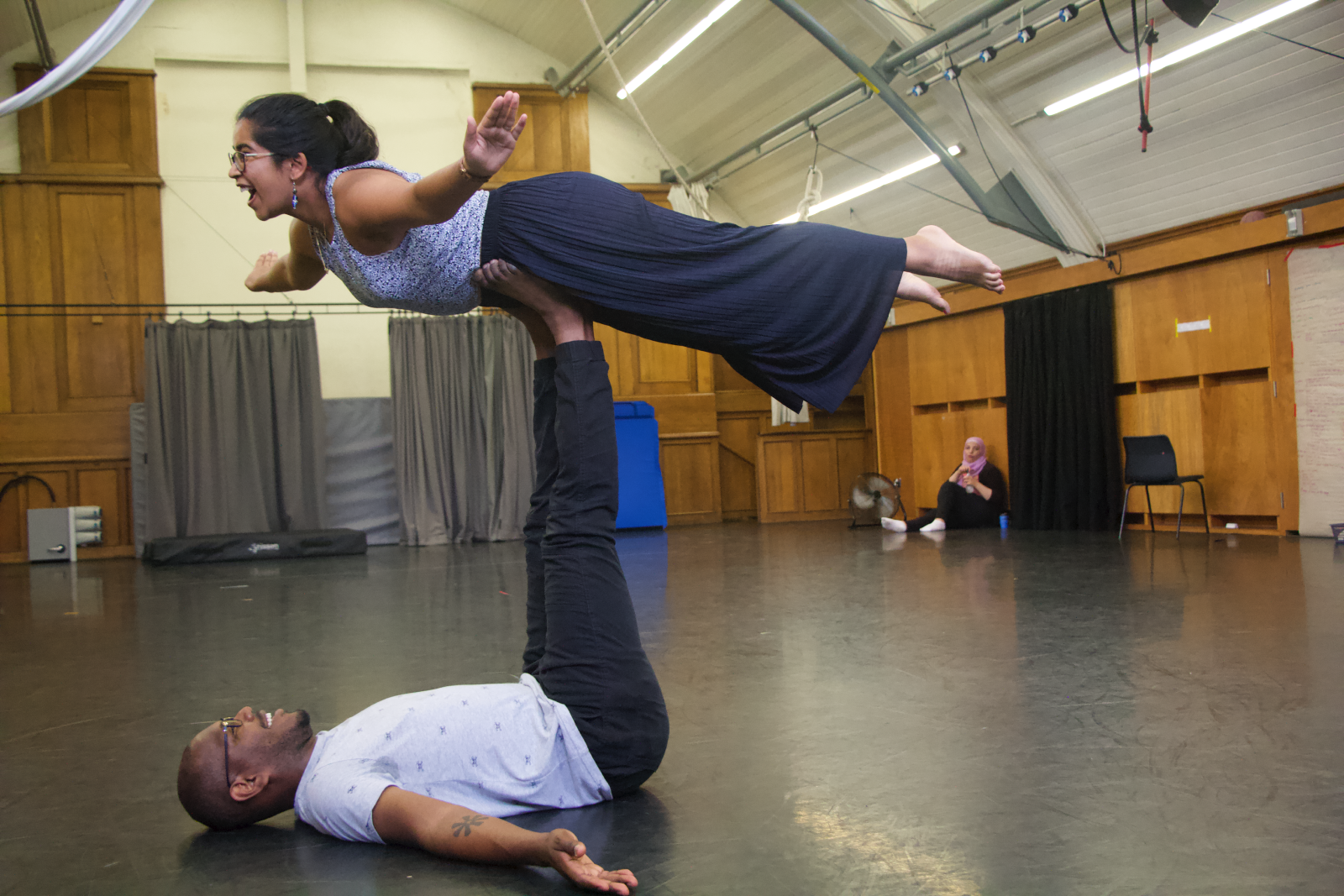 a young man holds up a young woman on his feet in a yoga pose